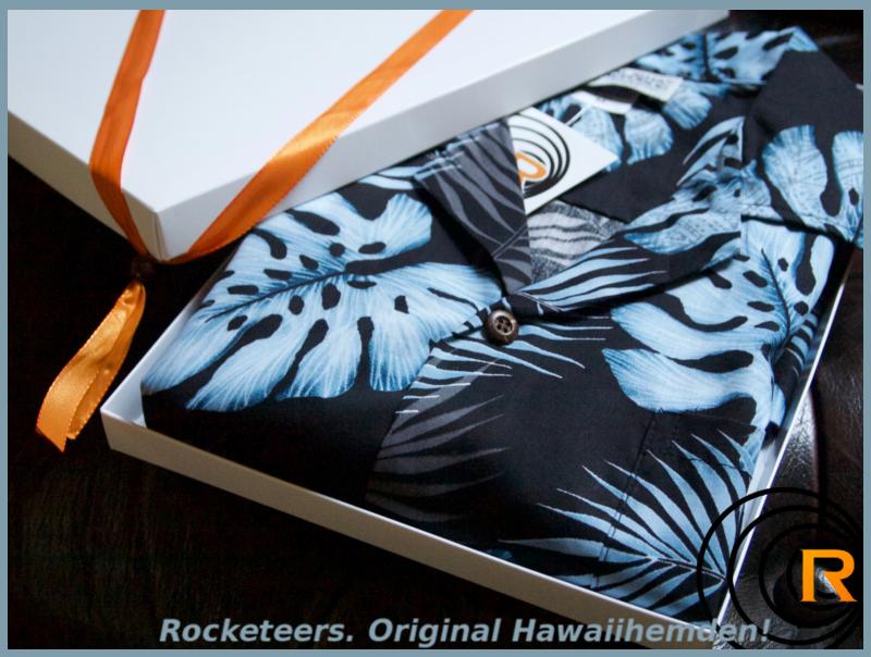 Das Bild zeigt original Hawaiihemd Blue Moon im Genschenkekarton. Blau Schwarz gefalten.